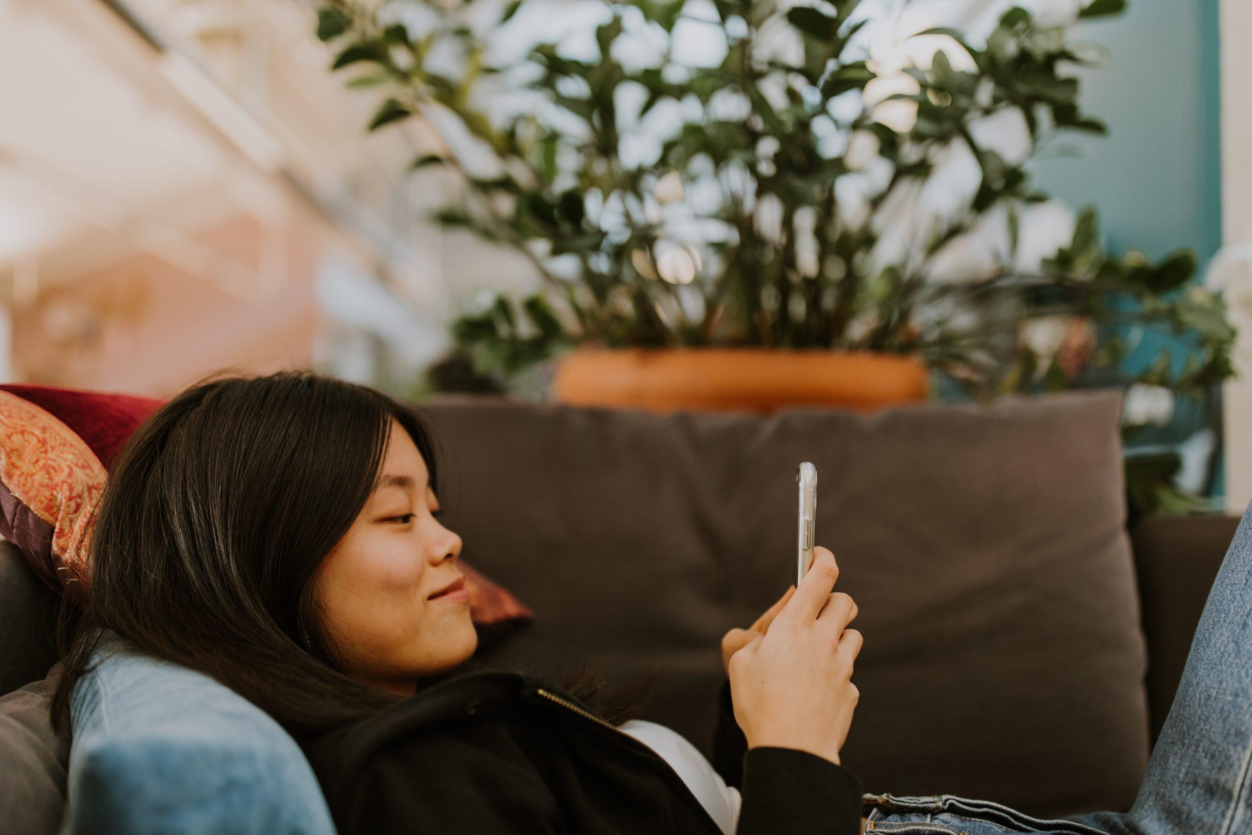 Flicka ligger i en soffa och tittar på en mobil
