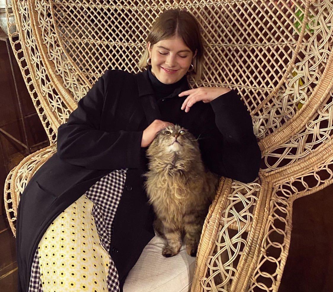 Sindra sitter med en katt i en stor fåtölj